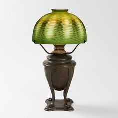 """This is not contemporary - image from a gallery of vintage and/or antique objects. """"Favrile"""" Tiffany Lamp  A Tiffany Studios New York patinated bronze and Favrile glass desk lamp featuring a green """"Damascene"""" shade with iridescent decoration atop a decorated four-footed urn base."""