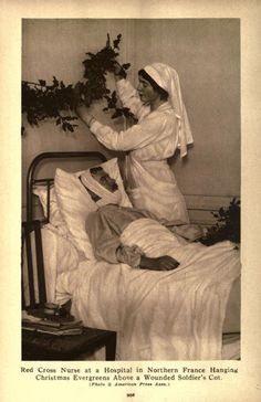 WW1. A Red Cross nurse in a hospital in Northern France hanging Christmas evergreens over a wounded soldier's cot.