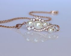 Tilly rose gold pearl necklace has been created in a modern-vintage cascading design with sparkling Swarovski zircon crystals and ivory white shell pearls for an elegant and sophisticated accessory. Perfect for whether youre wearing vintage, modern or a classic style wedding dress.  Our Tilly design is exclusive to Jamjewels, and we have a beautiful coordinating bracelet and earrings for the complete look!  ★★A crystal teardrop can be added to the bottom of the pendant to match the earrings…