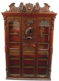 An Unusual American Folk Art Bookcase.  A unique bench made piece circa 1880. Rectangular with two glass doors, the central panel with high relief carving of an armoured bust in profile with an array of weapons issuing from all points. Each corner features a similar figure of a mermaid, the cornice is centered by a castle decorated shield flanked by kneeling Roman soldiers. Walnut, burled walnut veneer, poplar.