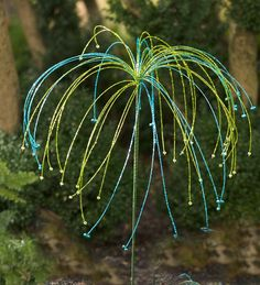 Buy it here for $29.95 or buy glass bead and outdoor-safe wire to make one yourself. It looks like a sea urchin or sea grasses. | Handmade Beaded Glass Garden Stake With Bells