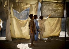 Afghan boys study at a makeshift school in the village of Budyali, Nengarhar Province, Afghanistan, Tuesday, March 19, 2013. (Photo by Anja Niedringhaus/AP Photo)