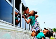 Female soldier kisses one of her daughters as she heads off to Afghanistan.  Her husband is a soldier also-MSN Photos