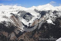 A beautiful view of high altitude peaks covered in snow and a nice valley in the middle strating between two rocky ridges with no snow left and continuing to the top of the mountains Winter Scenes, Mount Everest, Middle, Clouds, Snow, Stock Photos, Mountains, Nice, Photography