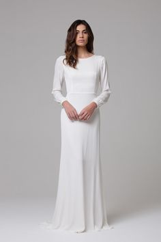 Celeste by Ivie White Be swept away in a celestial romance. This gown simplistic in its design, is nothing but. The Celeste, with its loose tapered sleeves, modest high neckline and low V back line, offers an understated beauty. Celeste is  effortless in form creating a silhouette you will feel incredible in.The addition of its gold hardware detail, gives the Celeste a special flair like no other.