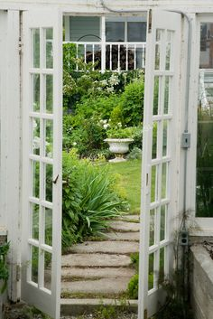 View from inside the Victorian-looking greenhouse behind the farmhouse on this property about one hour north of Seattle in the Skagit Valley, looking out to the Sissinghurst-style white garden that includes white delphiniums, white peonies, white climbing and shrub roses, and bleeding heart, among others. The greenhouse itself was salvaged and reclaimed for use from an arboretum in the region. Garden design by Toni Christianson, Christianson's Nursery