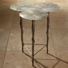 The Global Views Trois Lily Pad side table gives rise to an eclectic organic shape. Transitionally chic, the furnishing's triangular legs boast unexpected vine-like embellishments. 24.5in Dia x 24in H; Iron; Antique nickel finish