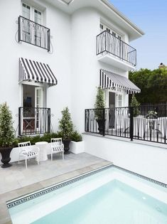 Black And White Greek Key Pool Tile, Black And White Striped Awning And Chairs, Greg Natale House Design, House, Pool Tile, Windows Exterior, House Exterior, House Styles, Exterior Design, Window Awnings, Pool Houses