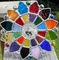 A faceted glass crystal prism hangs in the center of this colorful stained glass suncatcher. Shades of red, purple, blue, yellow, green, orange, pink and amber glass surround the prism. Some glass is textured, while other pieces are smooth. Six colored and six clear mini glass nuggets
