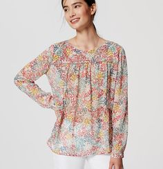 With a flowy fit, featherweight feel and flourishing floral print, this blouse is the freshest pick. Round neck. Long sleeves with button cuffs. Piped front and back yoke. Back button keyhole.