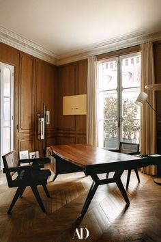 Designed by Isabelle Stanislas, the French interior designer worked with her bachelor client to fulfill his lifelong pied-à-terre dreams. In the office sits an Ico Parisi desk, vintage Pierre Jeanneret chairs, and a floor lamp by Georges Frydman. #offices #homeoffice #design #decor #officchairs #vintage #desk #minimalist #floorlamps #lamps #pierrejeanneret #chairs #art #artwork #windows #curtains Apartment Interior, Apartment Design, Room Interior, Interior Garden, Interior And Exterior, Parisian Decor, Interior Decorating, Interior Design, Paris Apartments
