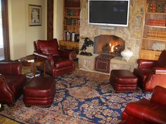 The lustrous lamb's wool, spacious design and glowing sapphire blue field of this first-rate Mahajiran Sarouk Persian rug adds to the comfortable ambiance of the library in a desert home. Also, the tribal Persian Kurdish Soumac saddlebags draped over the hearth enhance the casual, yet refined ambiance of this space.