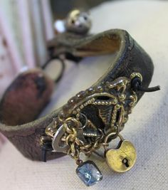 leather belt turned into Boho style bracelet .....I like how the charm is tied thru the back with leather rope
