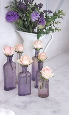 Pretty assortment of glass bottles used as vases, clever.
