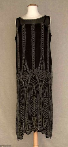 Black silk chiffon, sleeveless, clear crystals beaded in vertical stripes, waist to hem beading becomes heavier, more complex, lattice filled circles, half moons & gothic arches.  augusta-auctions.com