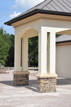 Elegant Arched Portico with Stacked Stone Base and a Standing Seam Metal Roof.
