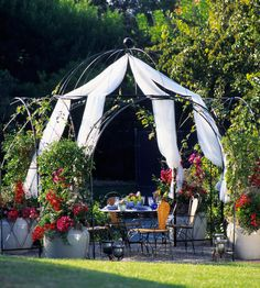 An elegant iron gazebo sports mandevilla vines in pots that anchor the edges, and wisps of white mosquito netting give this outdoor dining room a decidedly romantic flair.