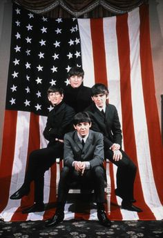 The Beatles clockwise from top John Lennon Ringo Starr Paul McCartney and George Harrison pose for a portrait in front of an American Flag in 1964 in...