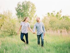 couple walking in a field on their engagement session