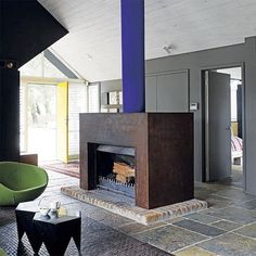 Being smitten with rusty steel, we love this solution to a rather homely exposed brick fireplace: cover it in sheets of intentionally-rusted cor-ten steel(also known as weathering steel)and paint the flue blue.