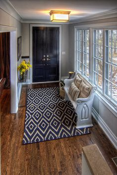 A dark rug is an excellent idea for a high-traffic area. The old church pew has been painted white and looks beautiful against the geometric print. The antique detail on the pew ties in nicely with the crown molding and trim. This is a great example of how blending traditional furniture with a modern print works well to keep an entryway from feeling too formal.