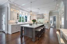 White kitchen & gray island <3. Love the floors. Different lights, different paint & different backsplash