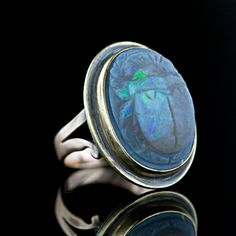 Unusual carved scarab motif opal cabochon set in a yellow gold bezel appliqued to a 10 karat rosy gold ring shank, circa 1900. The opal weighs approximately 9.00 carats and displays a gray-black body color with flashes of violetish-blue and green.