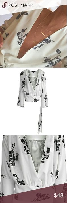 NEW LISTING! Flower, wrap top Gorgeous, black and white wrap top. Deep V neck and bell sleeves. Sash ties at waist. Can easily transition from day to night with adding a camisole or body suit. I paired with a bralette in last picture. Polyester/chiffon. Price is FIRM for this item! Tops Blouses