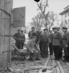 Churchill sits on one of the damaged chairs from Hitler's bunker in Berlin, 1945.