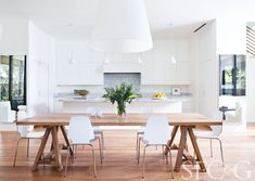 Ikea Vilmar chairs surround an RH trestle table in the dining area. A visually weightless FontanaArte Amax pendant chandelier helps to preserve the spare beauty of the space.