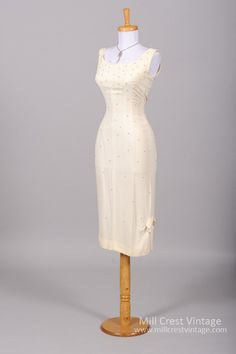 Designed in the 60's, this wonderful wiggle style vintage wedding dress is done in a cream toned silk crepe adorned with rhinestones. The sleeveless bodice o...