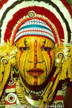 Head-dress and facial decoration on Mekeo youth, Papua New Guinea. Mekeo people come from the eastern parts of the Gulf Province and the western parts of the Central Province in south-central PNG. Their spectacular costuming (=bilas=decoration) favours use of bright yellow on face and body. Head-dresses are a characteristic shape and made from feathers of the Eclectus Parrot (red), Sulphur-crested Cockatoo (white) and domestic fowl (black). The round decorations are mother of pearl shell or…