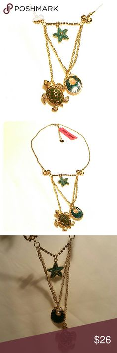 """Betsey Johnson Sea Turtle, Starfish Shell Necklace New with tag Betsey Johnson necklace in shiny gold metal with enameled green sea turtle with crystal rhinestone eyes, flippers, & back, a teal seashell with faux pearl, and teal starfish with aurora borealis crystal in center hanging from rhinestone chain across. Chains suspended by 2 bows with crystals in center, fine ball chain, BJ Heart on extension chain. 19"""" plus 3"""" extension.   Thank you for checking out my closet, and happy poshing…"""