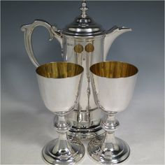 An Antique Victorian Sterling Silver communion service composed of a flagon and two goblets. The flagon in an early 17th century style having a straight-sided body, a scroll handle, a hinged
