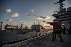 PHILIPPINE SEA,Dec.2,2013.Gunner's Mate 1st Class Adrian Lopez,from Chino,Calif.,foreground, shoots shot line from aircraft carrier USS George Washington (CVN 73) to Military Sealift Command dry cargo & ammunition ship USNS Charles Drew (T-AKE 10) for ammunition off-load.George Washington & embarked air wing,Carrier Air Wing (CVW) 5,provide combat-ready force to protect & defends collective maritime interest of US,allies & partners in  Indo-Asia-Pacific region(Mass Comm Spec Seaman Liam…