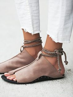 White linen trousers with frayed hem, worn with rope-tie brown leather sandals