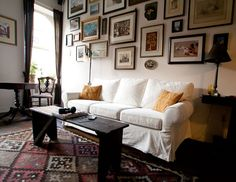 gallery wall and slipcovered couch in a cozy living room, via Apartment Therapy