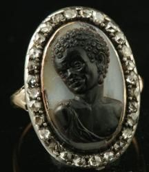 "An 18th century silver-topped gold and diamonds cameo ring. The oval closed-back bezel is set with a rare ""moretto"" cameo, carved in a sardonyx, framed by a rose-cut diamond border. Plain hoop, the split shoulders decorated with croziers and fleurons. The back of the bezel is chased with a radiant design"