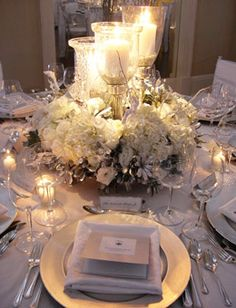 Brides Magazine: White Winter Wedding Flower Ideas  --  A trio of crystal and silver hurricanes are planted into a lush bed of white hydrangea, lisianthus, Vendela roses, flocked birch branches, silver lacquered pittosporum and wired crystals. R. Jack Balthazar    Photo: Courtesy of R. Jack Balthazar, Inc.
