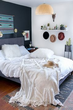 California modern bedroom - love the brass sconces and dark grey accent wall up against the bed.