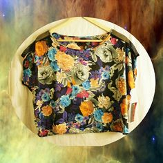 Floral boxy crop top NWT Bright & fun mixed floral pattern silky box crop top. Black base with greys, blues, pinks, purples and light coral-orange colors in design. Fishnet style mesh down sleeves from shoulders. This shirt is SO light.. it weighs like, nothing at all. Made of polyester but feels like thin satin. Made by Bongo, NWT. Size Large. BONGO Tops Crop Tops