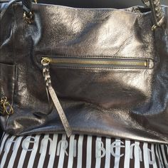 Henri Bendel brand new purse Brand new authentic HENRI BENDEL HANDBAG....Metallic silver with gold hardware. Two pockets on the side one zipper pocket in the front. Four pockets on the inside. Lined inside with royal blue satin. Limited addition purse. henri bendel Bags Shoulder Bags