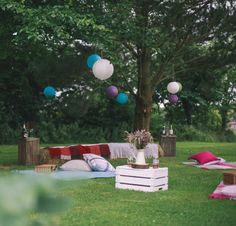 A perfect chill out area in the garden.  Upturned crates for tables, blankets on hay bales for extra seating and picnic blankets.