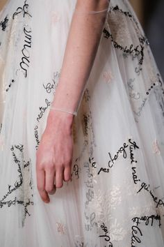 """This woman's skin is shimmering and pale, her long black hair is tied with dozens of silver ribbons that fall over her shoulders. Her gown is white, covered in what to Bailey looks like looping black embroidery, but as he walks closer he sees that the black marks are actually words written across the fabric. When he is near enough to read parts of the gown, he realizes that they are love letters, inscribed in handwritten text. Words of desire and longing wrapping around her wai..."
