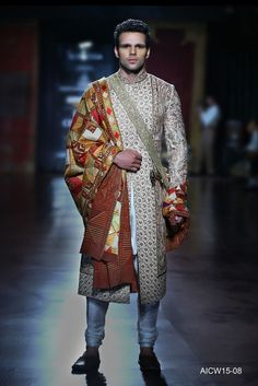Ivory silk sherwani featuring delicate resham and kasab embroidery aired with a silk kurta-churidar