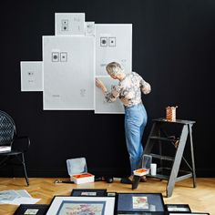 View of woman marking out design on wall with backing paper from RIBBA frames.