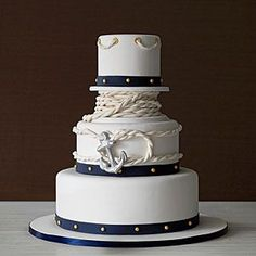 Coastal Wedding Cakes | Anchors Away: Covered in white fondant icing with navy bands and gold fondant studs, accented with a sailor's knot and anchor.