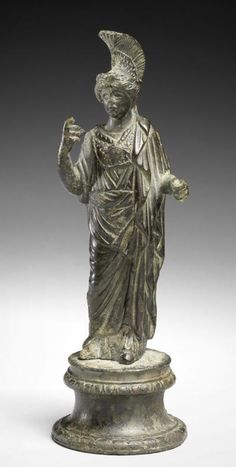 A Roman bronze figure of Athena  Circa 2nd Century A.D. The goddess standing with the weight on her left leg, draped in a long chiton with himation over the top, the aegis with gorgoneion at her chest, wearing a high crested Corinthian helmet pushed back on her head, her left arm in front to hold her shield, now missing, her right arm held up to hold her spear, now missing, 4½in (11.7cm) high, mounted