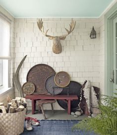 A basswood moose head was stationed on the front porch of this Maine cottage, where wood is stored in an Ikea basket. Country Living