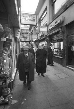 """Walkers Court 1978. Priests coincidentally walk under a """"Striptease"""" sign in Soho (AP)"""